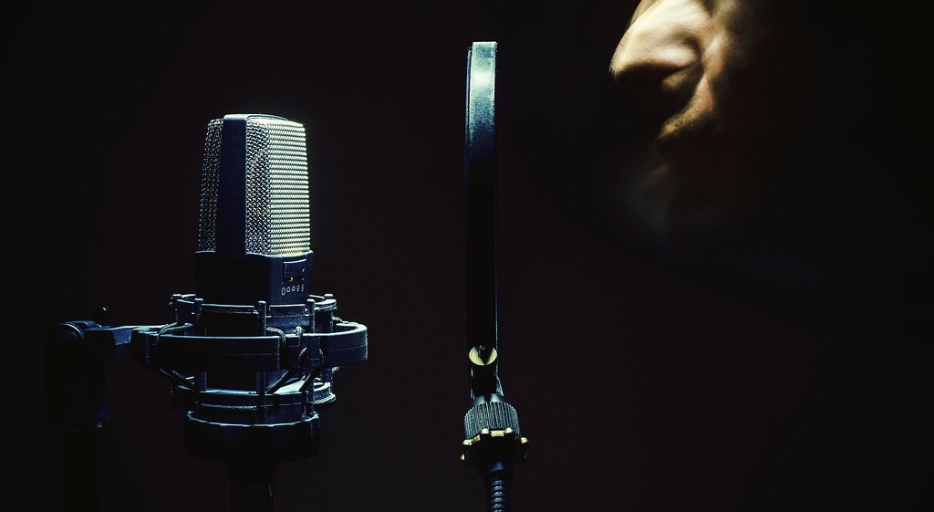 Man's face singing in front of a modern condenser microphone and popup filter.