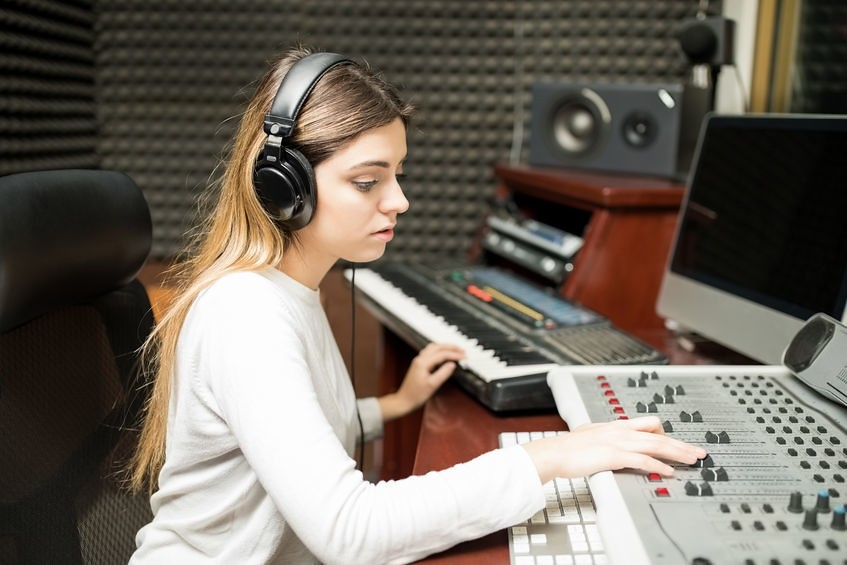 Female sound engineer composing music